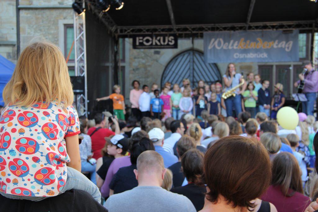 Weltkindertag Bühne mit Kindern und Musikinstumenten im Hintergrund. Im Vordergrund Zuschauer*innen. Ein Kind sitzt auf den Schultern.