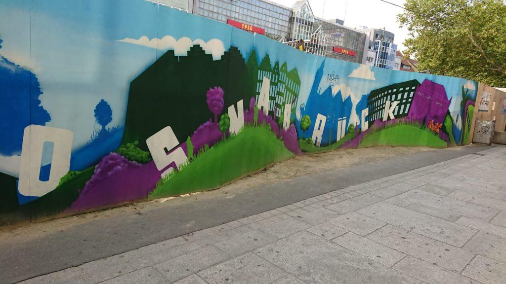"""Ein Graffito an einem Bauzaun am Osnabrücker Neumarkt. Es zeigt eine hügelige Rasenlandschaft, über die sich der Schriftzug """"OSNABRÜCK"""" schlängelt. In lila und blau sind auf dem Graffito die Umrisse der Marienkirche und des Rathauses zu erkennen."""