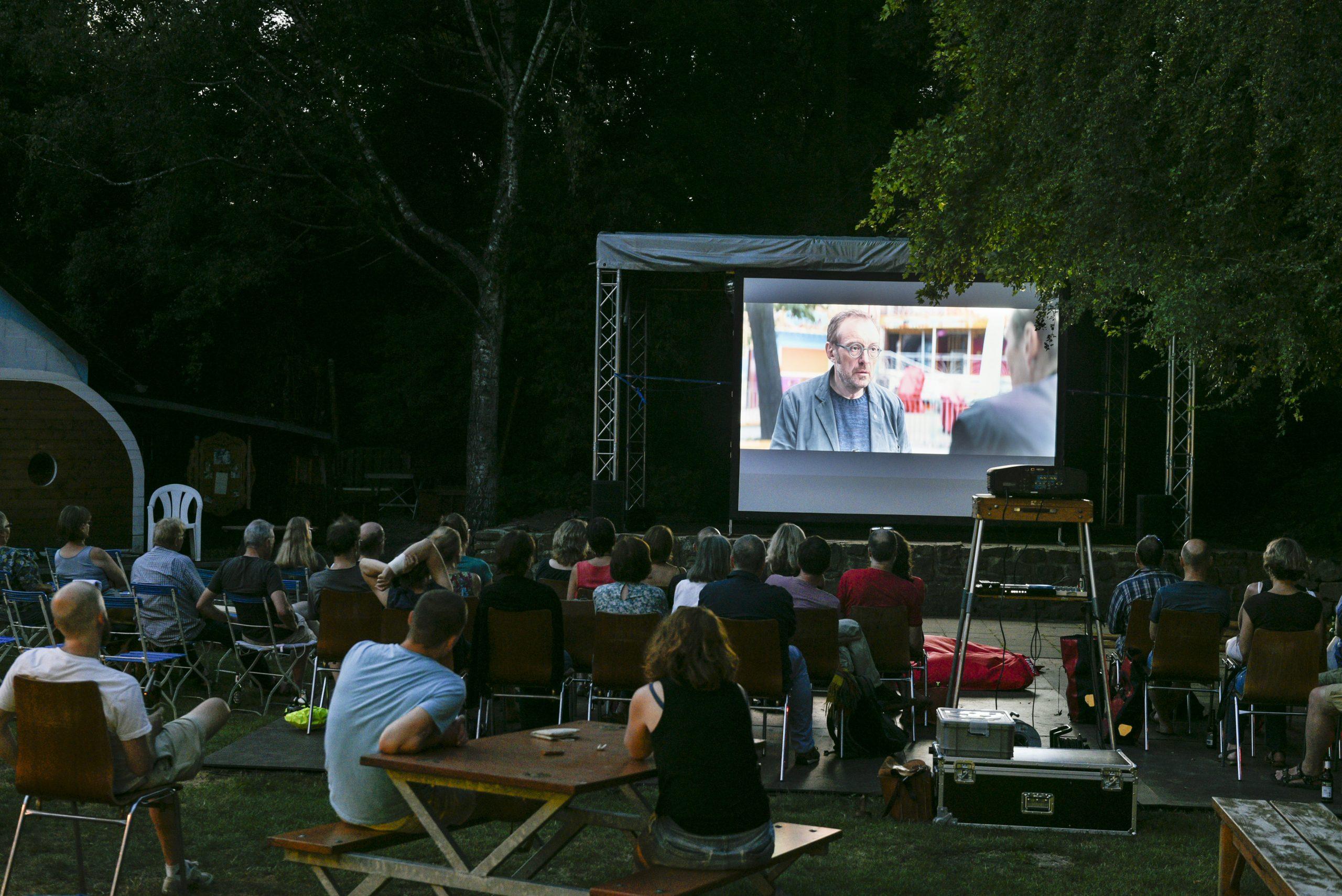 """Open Air-Kino-Situation. Zuschauer sind im Dunklen sitzend von hinten fotografiert, wie sie den Film """"Wilde Maus"""" auf einer großen Leinwand verfolgen"""